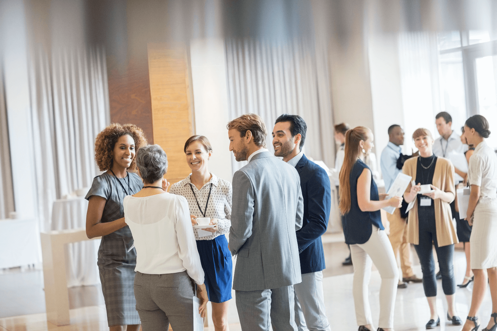 Image of professional employees, dressed in business casual, conversing in groups
