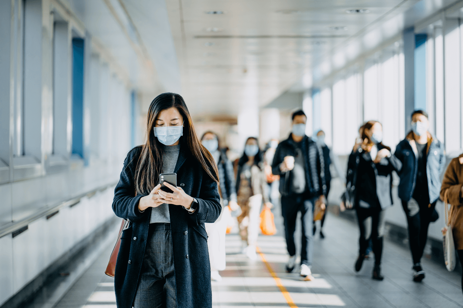 Image of people walking while wearing medical face masks