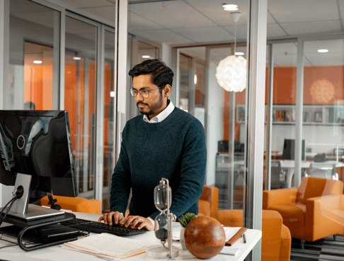 Photo of man with glasses by his standing desk typing on his computer in vibrant office setting