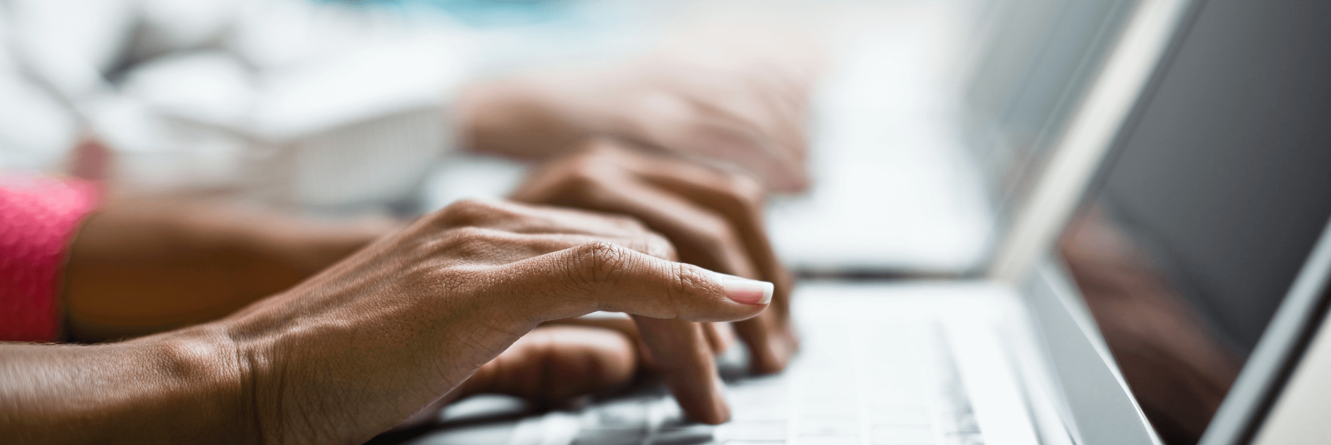 Close-up photo of woman's hands typing on laptop